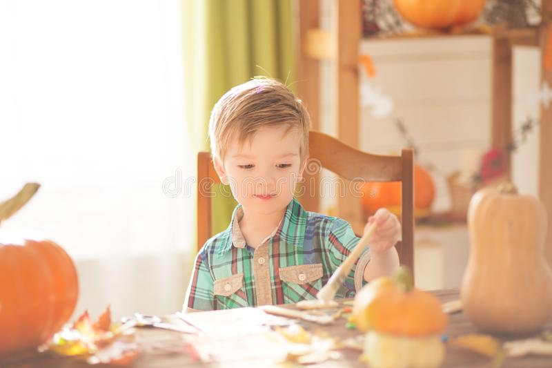 Happy Halloween concept. Cute little happy boy carving a pumpkin for halloween on a table indoors.  stock image