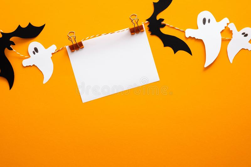 Happy halloween concept. Halloween decorations, blank paper card on clips, bats, ghosts on orange background. Halloween party. Greeting card mockup with copy stock photo