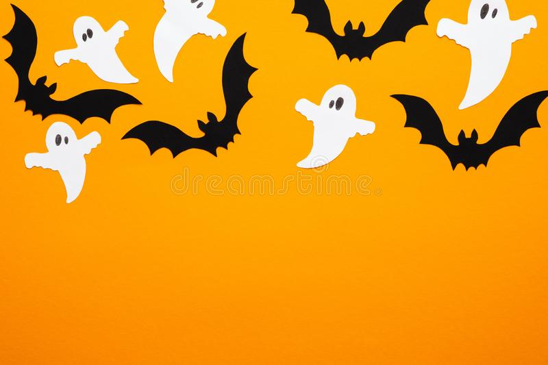 Happy halloween concept. Frame of Halloween decorations, bats, ghosts on orange background. Halloween party greeting card mockup. With copy space. Flat lay, top stock photography