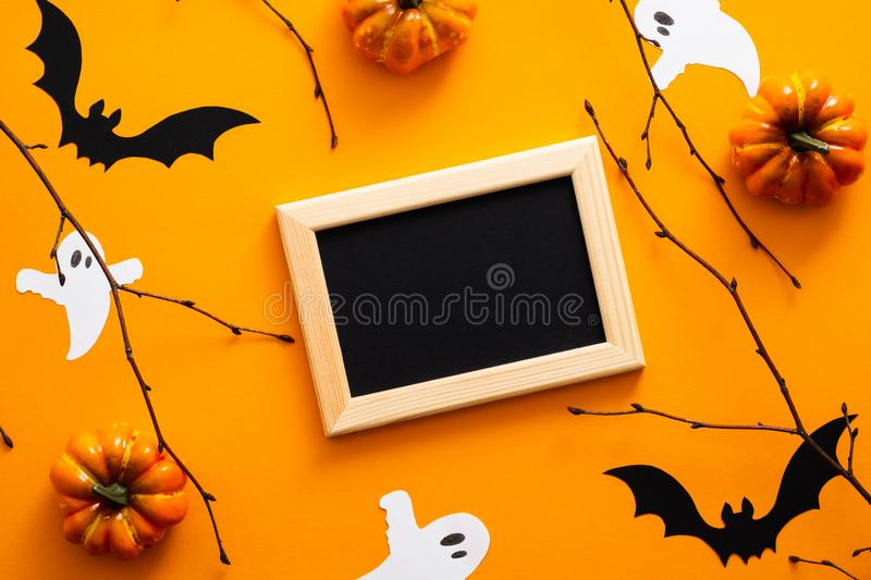 Happy halloween concept. Halloween decorations, picture frame, pumpkins, bats, ghosts on orange background. Halloween party. Greeting card mockup with copy stock images