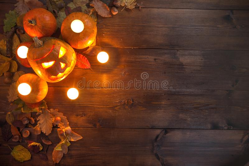 Happy Halloween! The concept of the holiday, autumn still life. Of small pumpkins that lie on dry leaves on a dark wooden background at the upper left border of royalty free stock image