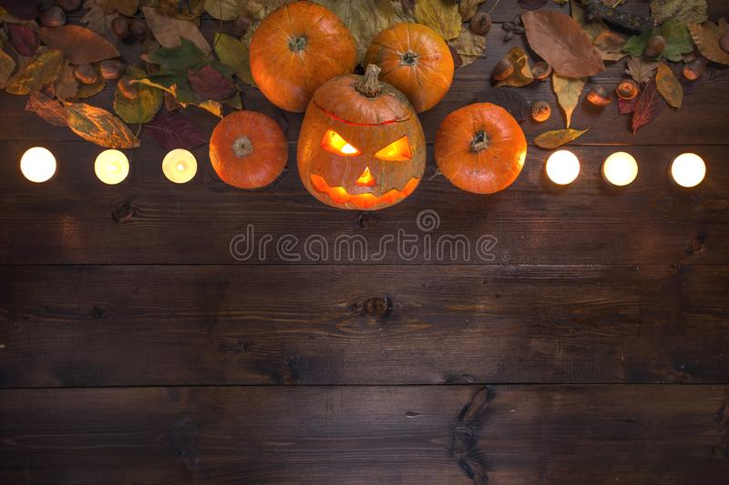 Happy Halloween! The concept of the holiday, autumn still life. Of small pumpkins that lie on dry leaves on a dark wooden background in the middle at the upper stock photos