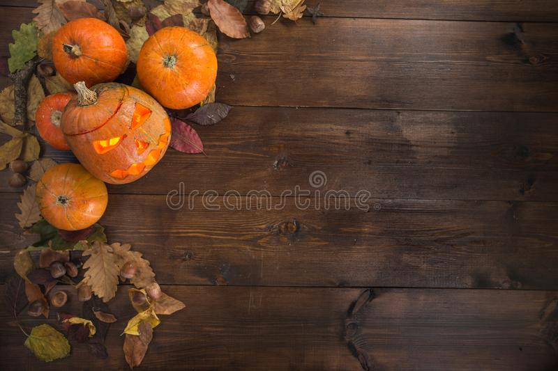 Happy Halloween! The concept of the holiday. Autumn still life of small pumpkins that lie on dry leaves on a dark wooden background. One pumpkin carved lantern stock photography