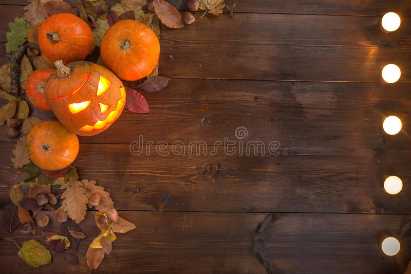 Happy Halloween! The concept of the holiday. The autumn still life of small pumpkins that lie on dry leaves on a dark wooden background and candles are lined stock images
