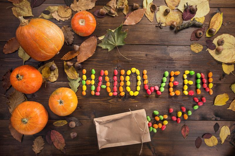 Happy Halloween! The concept of the holiday. The word `Halloween` laid out of scattered candy, autumn still life of dry leaves and five small pumpkins on a royalty free stock photos