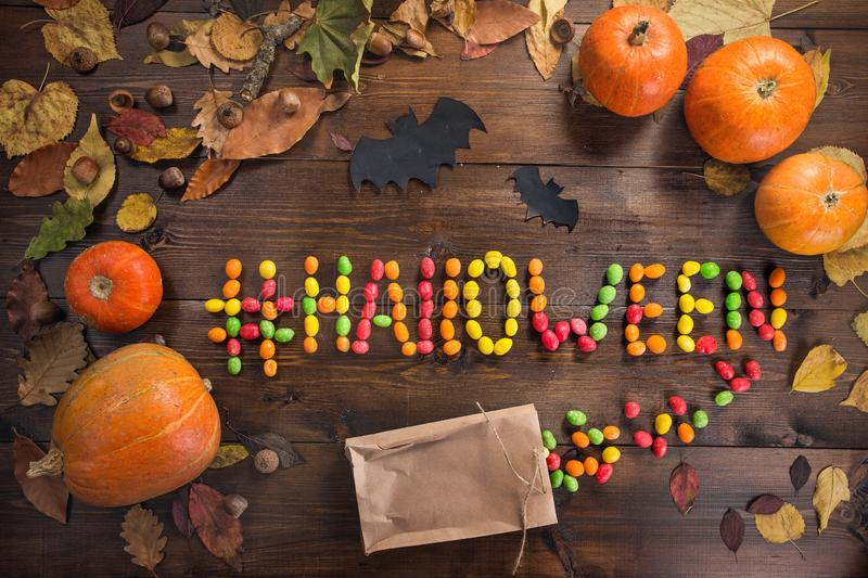 Happy Halloween! The concept of the holiday. The word `Halloween` with a hashtag lined with scattered chocolates, autumn still life of dry leaves and five royalty free stock image