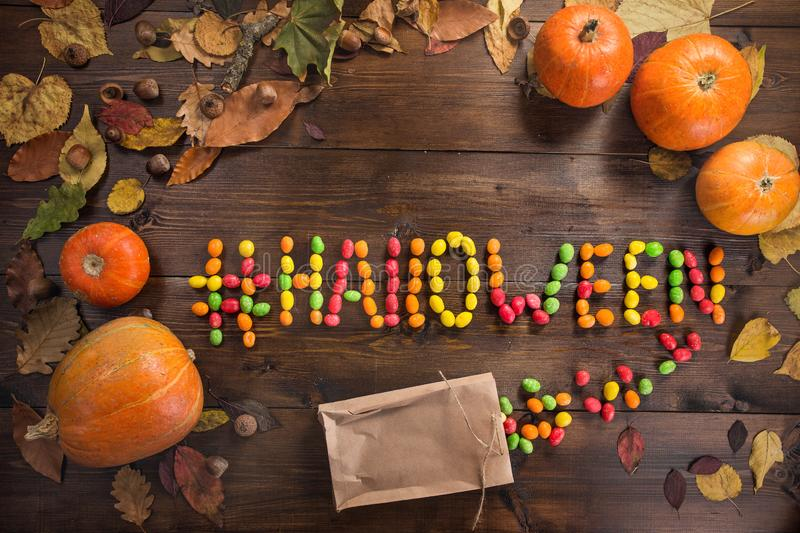 Happy Halloween! The concept of the holiday. The word `Halloween` with a hashtag lined with scattered chocolates, autumn still life of dry leaves and five stock images