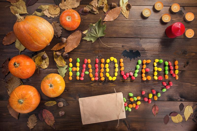 Happy Halloween! The concept of the holiday. The word `Halloween` laid out of scattered candy, autumn still life of dry leaves, candles and five small pumpkins royalty free stock photo