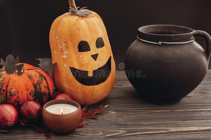 Happy Halloween concept. Pumpkins, jack-o-lantern, witch cauldron,bats, spider, candle light, autumn leaves on dark background. S royalty free stock photos