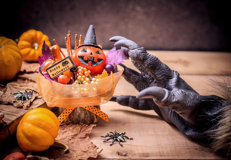 Happy Halloween concept. Happy Halloween. Werewolf or zombie hands making scary pumpkin gift for trick or treat party. copy space for text stock photos