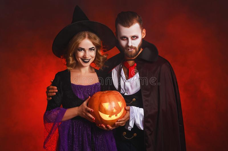 Happy Halloween!  couple man and woman  in a Dracula vampire and witch costumes  with  pumpkin on  glowing red background royalty free stock image