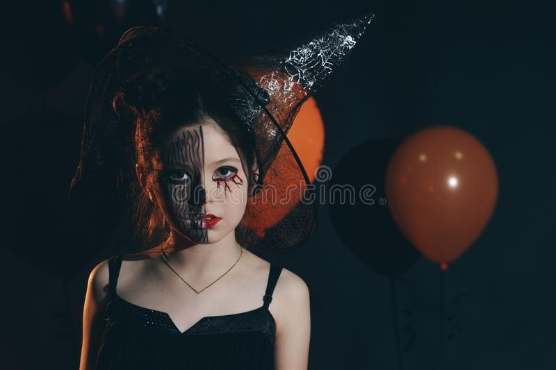 Happy Halloween Cute cheerful little witch with a magic wand and book of spells. Beautiful child girl in witch costume royalty free stock photos