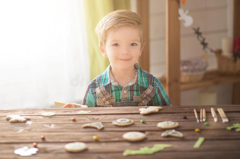 Happy Halloween. Cute funny happy boy covering cookies for Halloween cookies at home.  stock images