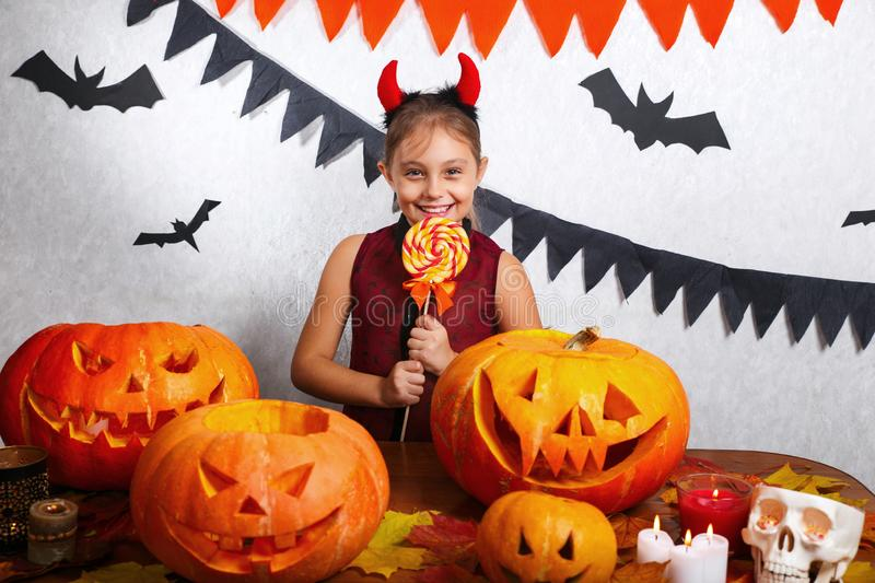 Happy Halloween. Cute funny girl with a pumpkin and candy. Happy Halloween. Cute little girl with a pumpkin and candy royalty free stock images