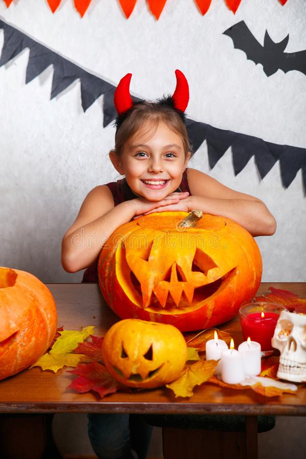 Happy halloween. Funny little child girl with carving pumpkin. Happy family preparing for Halloween. Happy halloween. Cute funny little child girl with carving stock photography