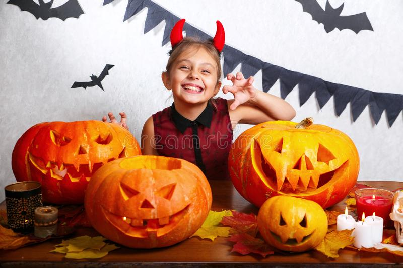 Happy halloween. Funny little child girl with carving pumpkin. Happy family preparing for Halloween. Happy halloween. Cute funny little child girl with carving royalty free stock photo