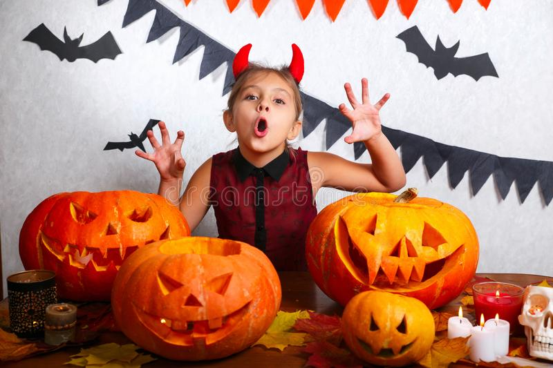 Happy halloween. Funny little child girl with carving pumpkin. Happy family preparing for Halloween. Happy halloween. Cute funny little child girl with carving stock images