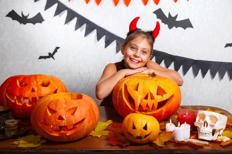 Happy halloween. Funny little child girl with carving pumpkin. Happy family preparing for Halloween. Happy halloween. Cute funny little child girl with carving royalty free stock photography