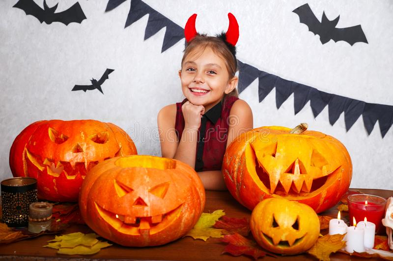 Happy halloween. Funny little child girl with carving pumpkin. Happy family preparing for Halloween. Happy halloween. Cute funny little child girl with carving stock photo