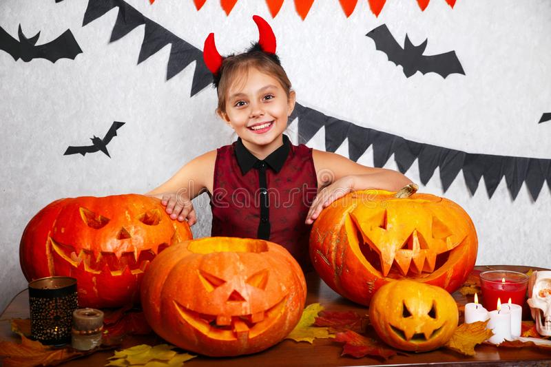 Happy halloween. Funny little child girl with carving pumpkin. Happy family preparing for Halloween. Happy halloween. Cute funny little child girl with carving stock photos