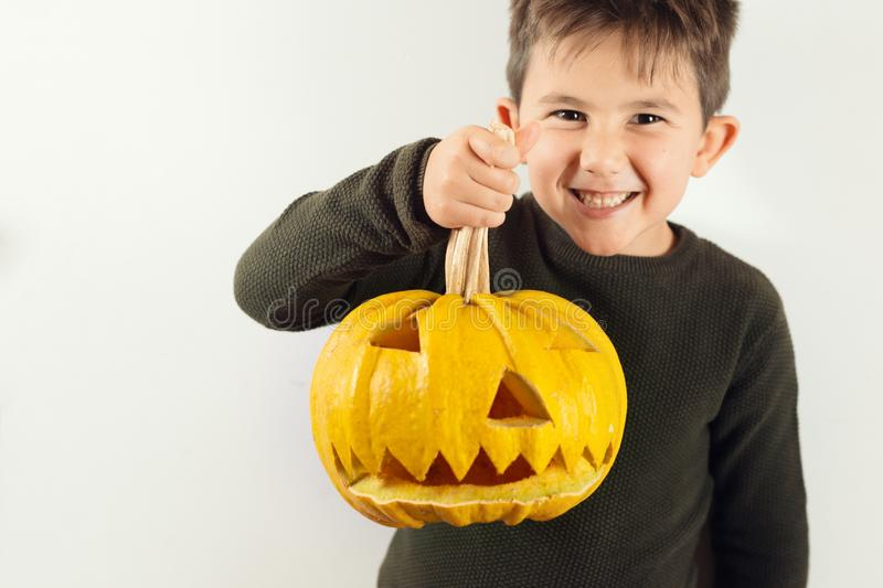 Happy Halloween Cute little boy with a pumpkin. Happy Halloween Cute little boy making funny faces with a pumpkin royalty free stock photography
