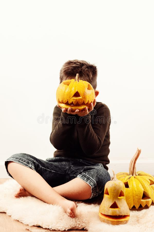Happy Halloween Cute little boy with a pumpkin. Happy Halloween Cute little boy making funny faces with a pumpkin royalty free stock images