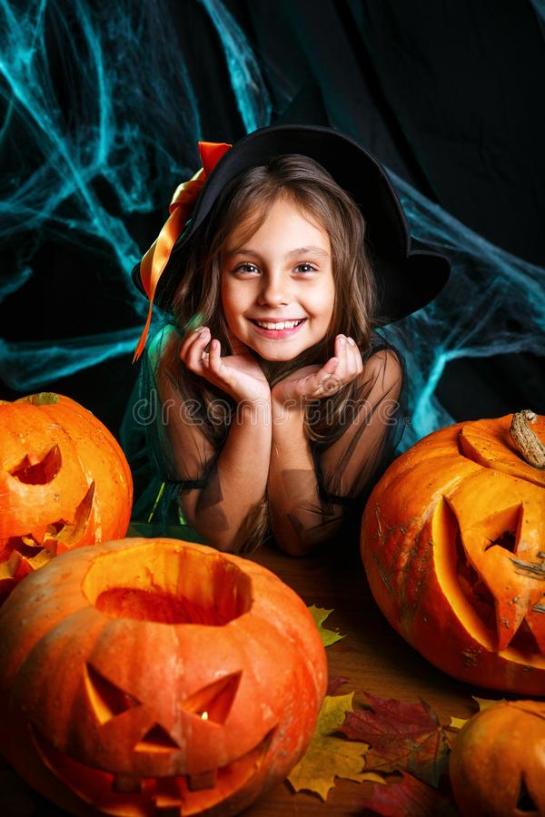 Happy halloween. Pretty little child girl in witch costume with carving pumpkin . Happy family preparing for Halloween. Happy halloween. Cute little child girl royalty free stock photo
