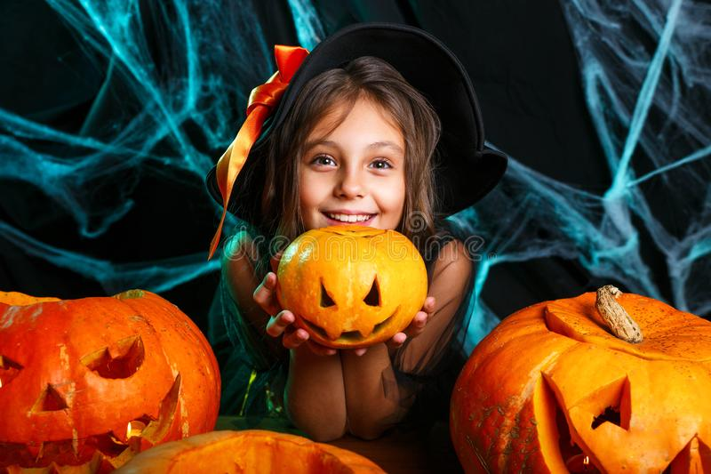 Happy halloween. Pretty little child girl in witch costume with carving pumpkin . Happy family preparing for Halloween. Happy halloween. Cute little child girl stock image