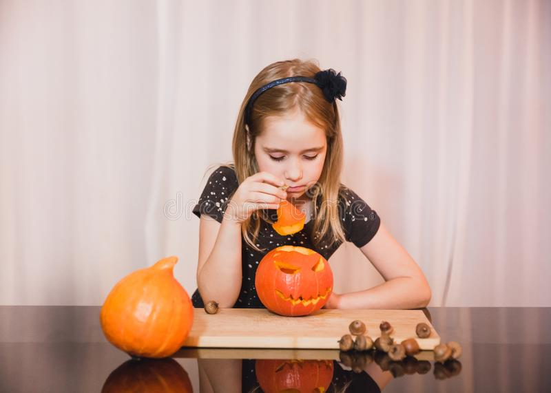 Happy halloween. Cute little girl look at the scary pumpkin. At home stock image