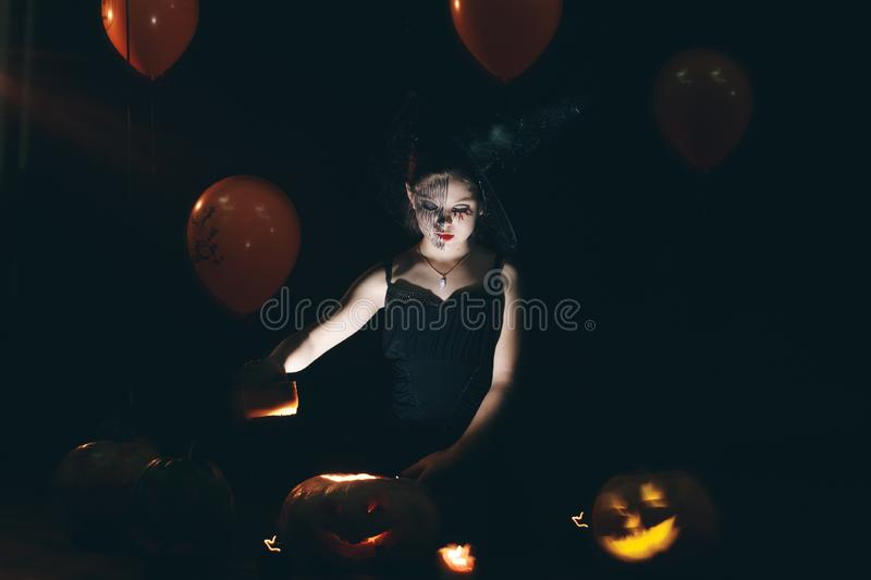 Happy Halloween Cute little witch with a big pumpkin. Beautiful young child girl in witch costume outdoors. stock image