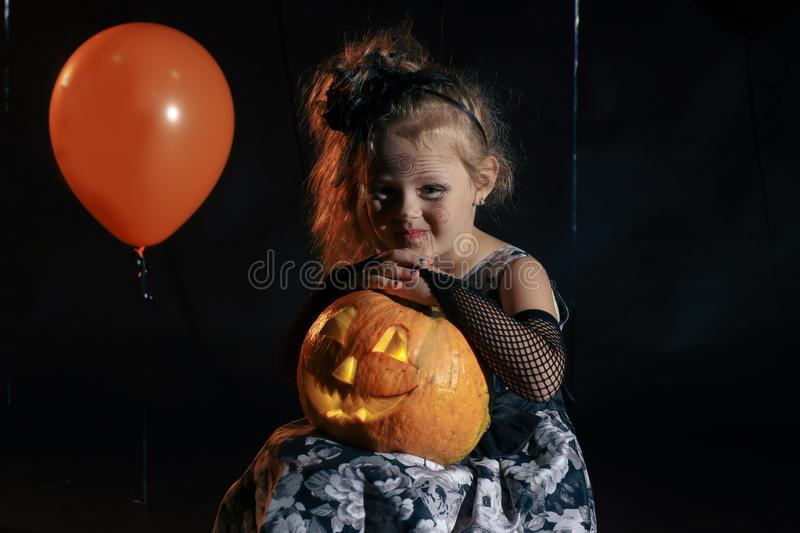 Happy Halloween Cute little witch with a pumpkin. royalty free stock photography