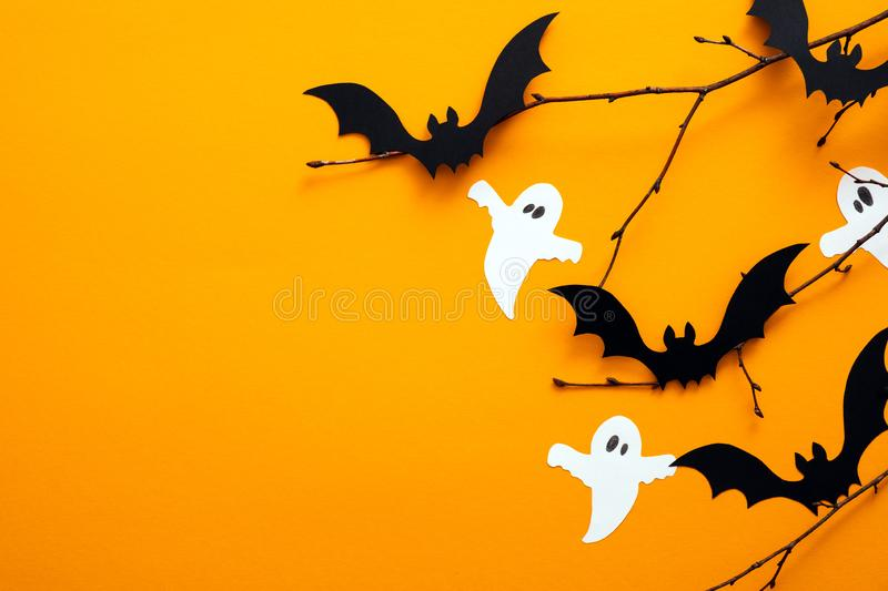 Happy Halloween day concept. Halloween decorations, paper ghosts, bats on orange background. Flat lay, top view, copy space. N royalty free stock photo