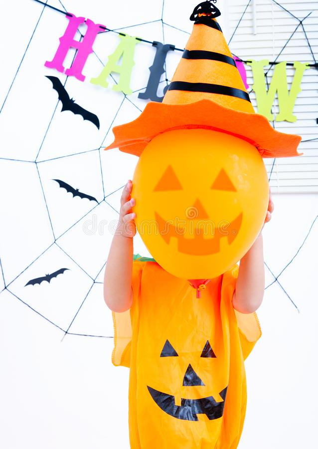 Happy Halloween Day. Little childhood holding orange face balloon pumpkin Jack have hat conceal faces stock photography