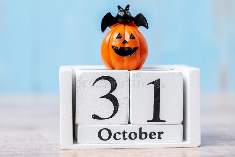 Happy Halloween day with 31 October calendar wood, jack o lantern pumpkin and bat decor with funny face on table background with. Copy space. Autumn season royalty free stock images