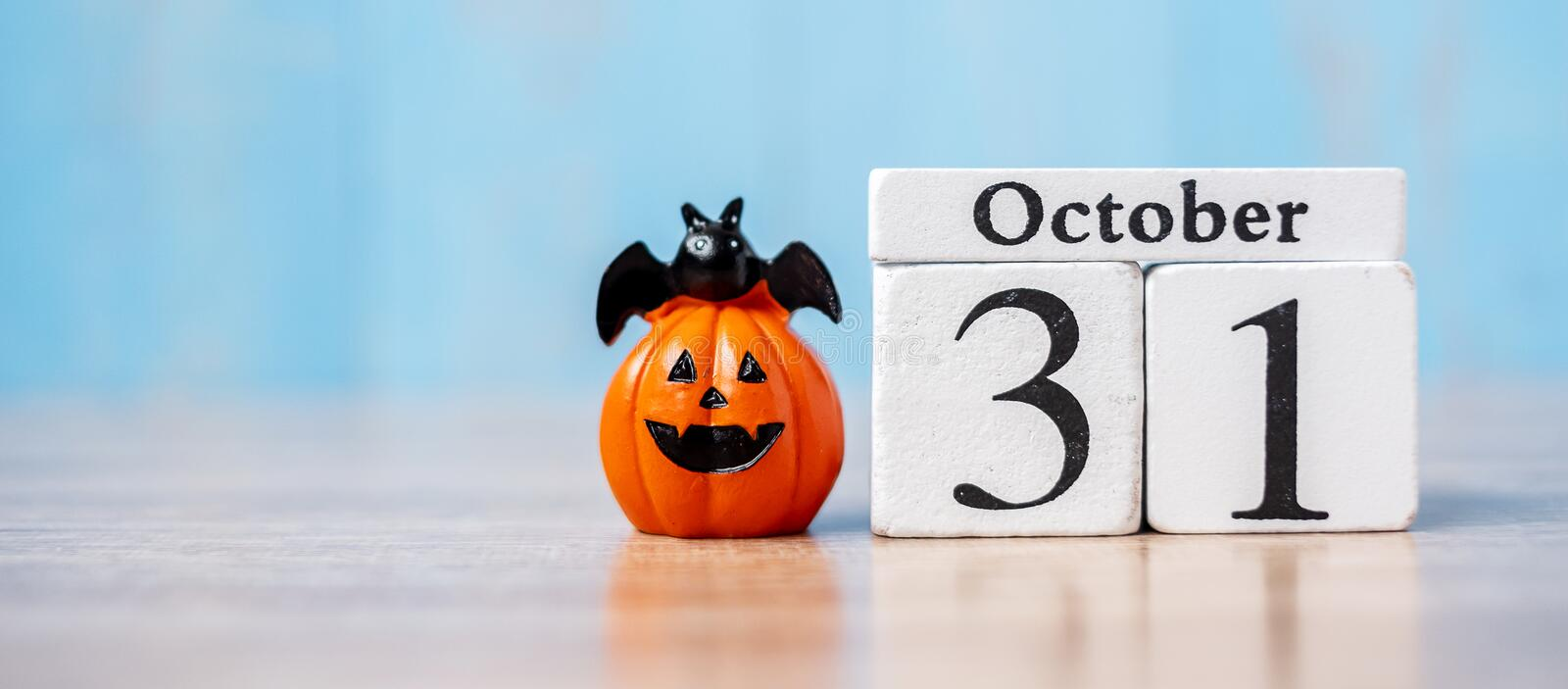 Happy Halloween day with 31 October calendar wood, jack o lantern pumpkin and bat decor with funny face on table background with. Copy space. Autumn season royalty free stock photo