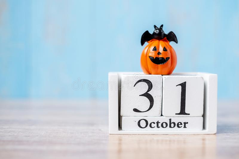 Happy Halloween day with 31 October calendar wood, jack o lantern pumpkin and bat decor with funny face on table background with. Copy space. Autumn season stock images