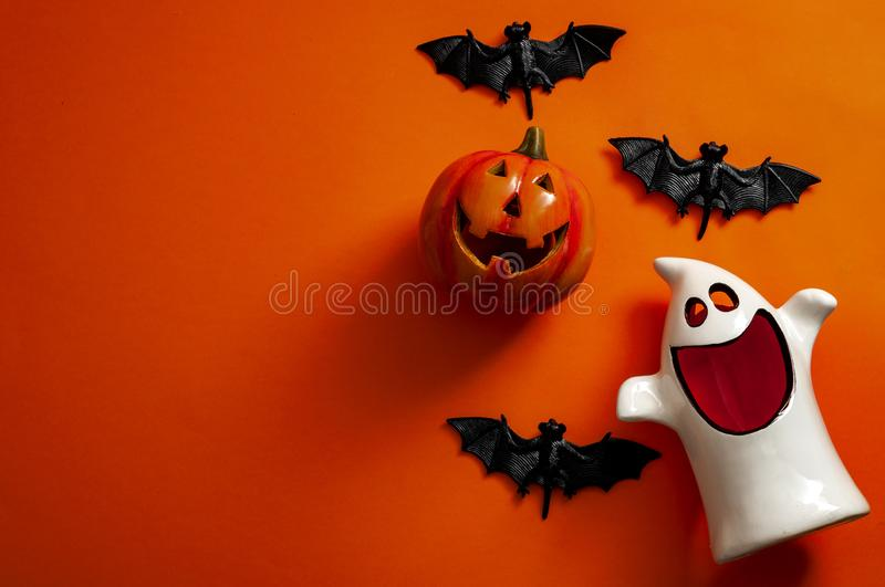 Happy Halloween and fall holiday concept with jack o lantern, bats and a ghost isolated on orange background with copy space. Happy Halloween and fall holiday royalty free stock photo