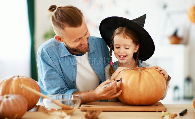 Happy Halloween! family  father and child daughter cut pumpkin for holiday at home. Happy Halloween! family father and child daughter  cut a pumpkin for holiday stock photography