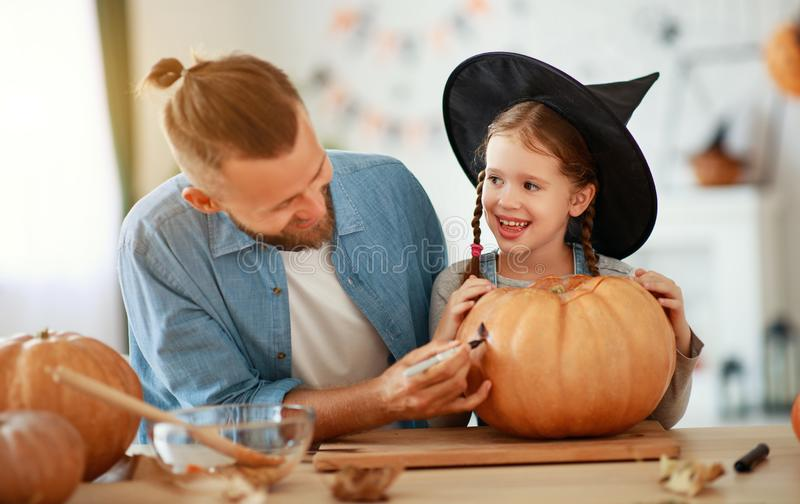 Happy Halloween! family  father and child daughter cut pumpkin for holiday at home. Happy Halloween! family father and child daughter  cut a pumpkin for holiday stock images