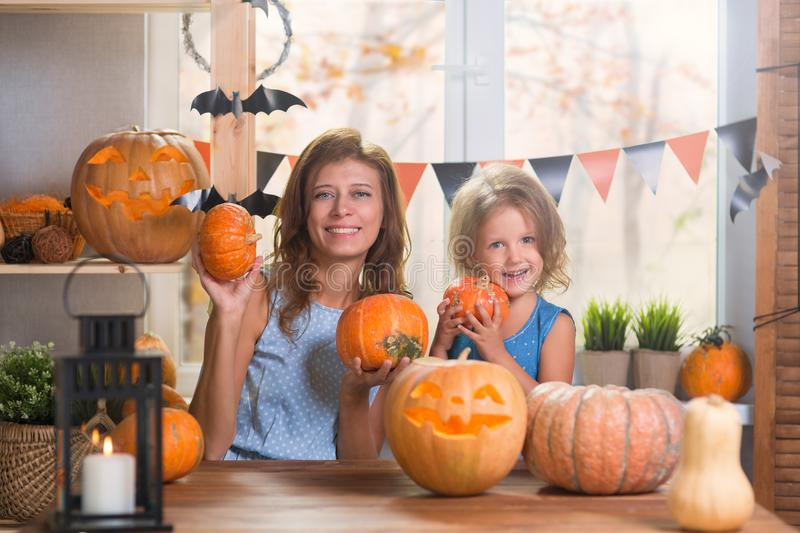 Happy Halloween. Family little beautiful girl with mother celebrating home with pumpkins stock photography