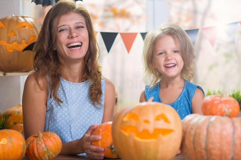 Happy Halloween. Family little beautiful girl with mother celebrating home with pumpkins stock photo