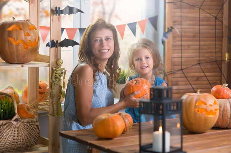Happy Halloween. Family little beautiful girl with mother celebrating home with pumpkins. Happy Halloween. Family little beautiful girl with mother celebrating stock photography