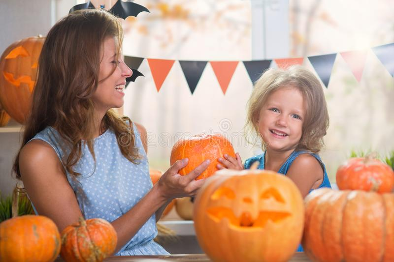 Happy Halloween. Family little beautiful girl with mother celebrating home with pumpkins. Happy Halloween. Family little beautiful girl with mother celebrating royalty free stock images