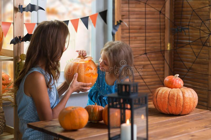 Happy Halloween. Family little beautiful girl with mother celebrating home with pumpkins. Happy Halloween. Family little beautiful girl with mother celebrating royalty free stock image