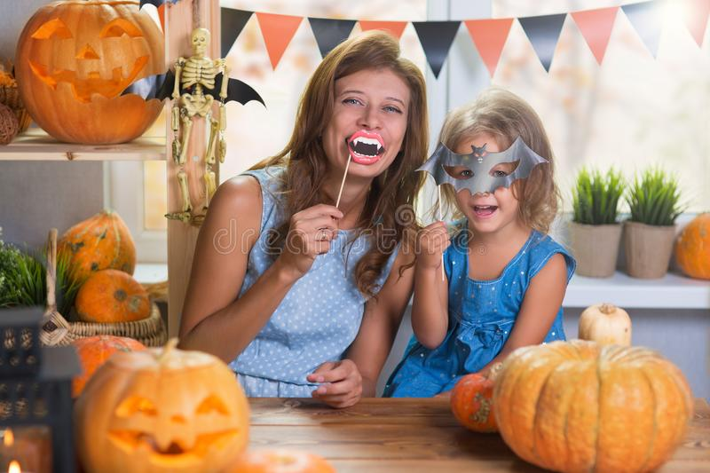 Happy Halloween. Family little beautiful girl with mother celebrating home with pumpkins. Happy Halloween. Family little beautiful girl with mother celebrating royalty free stock photos