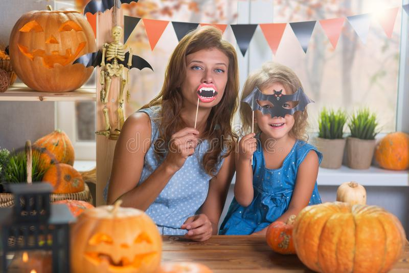 Happy Halloween. Family little beautiful girl with mother celebrating home with pumpkins stock photos