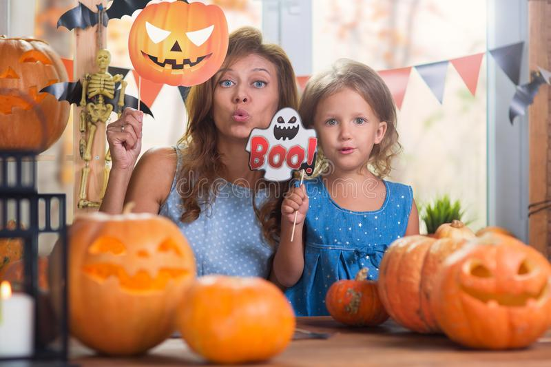 Happy Halloween. Family little beautiful girl with mother celebrating home with pumpkins royalty free stock photo