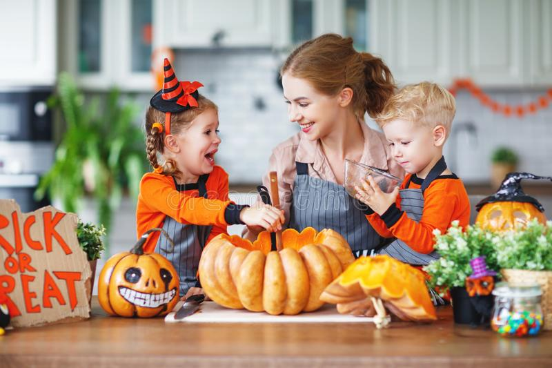 Happy Halloween! family mother and children getting ready for ho. Liday cutting a pumpkin royalty free stock image