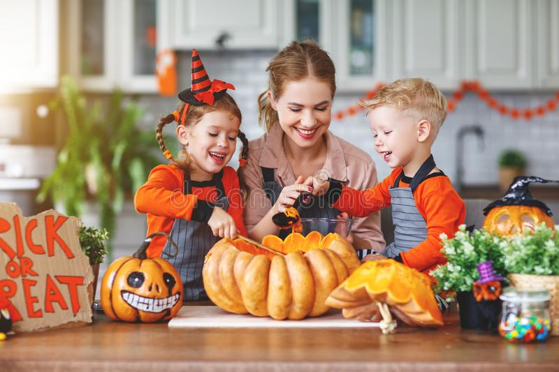 Happy Halloween! family mother and children getting ready for ho. Liday cutting a pumpkin royalty free stock photos