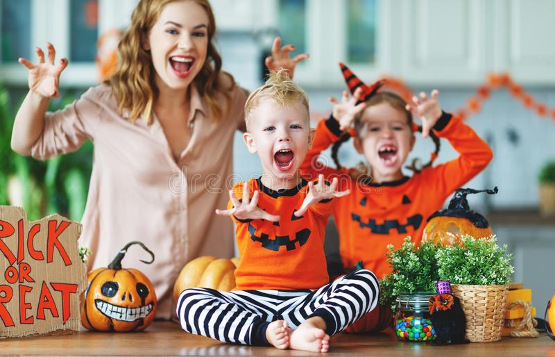 Happy Halloween! family mother and children getting ready for ho. Liday cutting a pumpkin royalty free stock photography